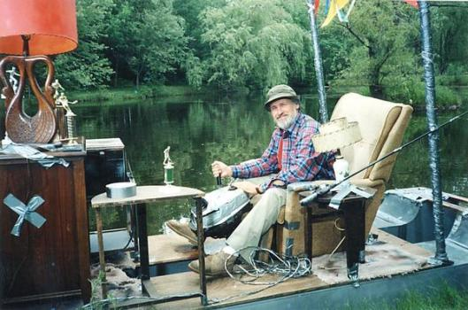 a picture of the character red green sitting in a home made open air living-room boat, constructed primarily using duct tape
