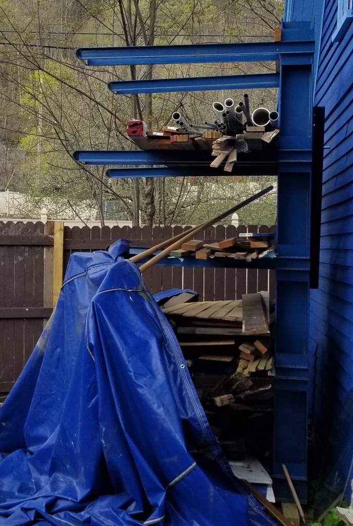 a blue wood rack, partially filled with wood, with a large - very heavy - blue tarp half draped over the bottom half.